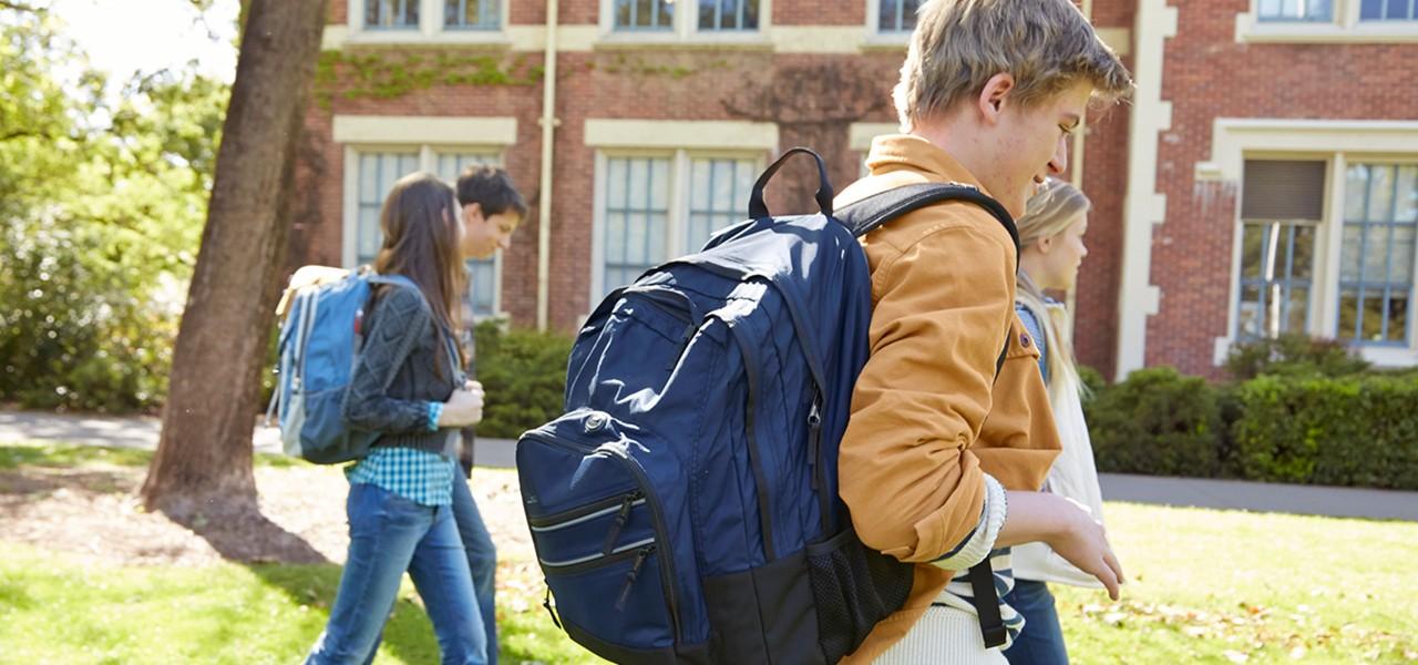 Several teens walking on school campus wearing L. L. Bean backpacks.