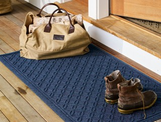 Close-up of a front door from the porch, a mat outside the door.