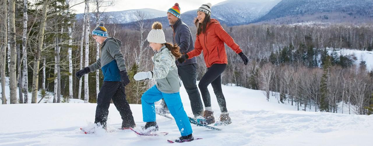 Family enjoying a snowshoe walk outside