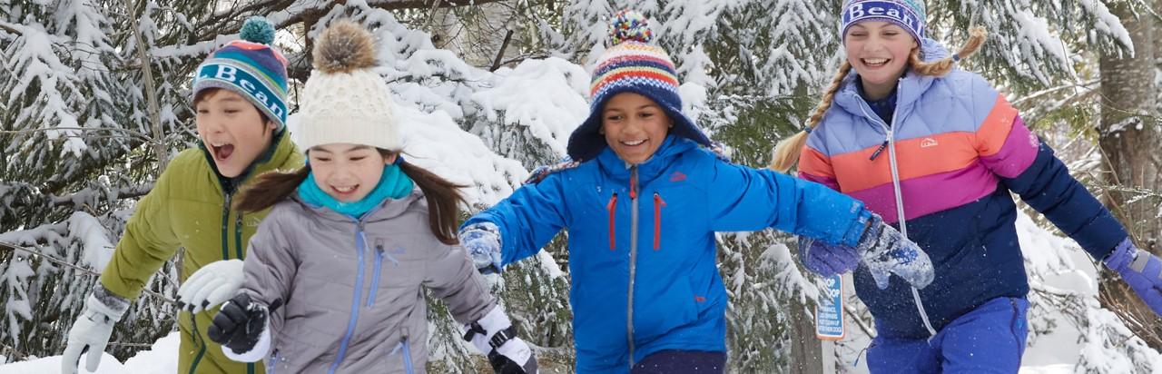Kids runnikg in snow covered woods